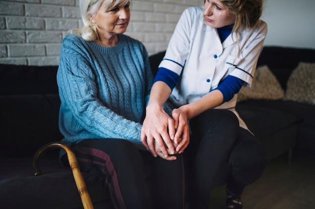 Conceito de aposentadoria em casa com a enfermeira cuidar da mulher