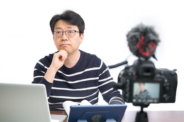 Conceito de aprendizagem on-line. um professor do sexo masculino asiático de meia-idade se preparando para aprender online.