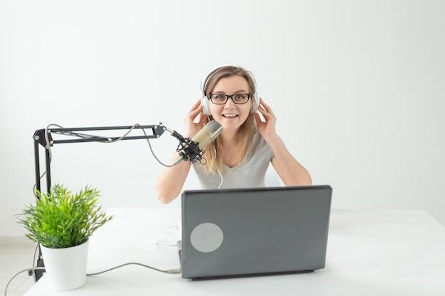 Conceito de apresentador de rádio - mulher trabalhando como apresentador de rádio sentada na frente do microfone sobre o branco