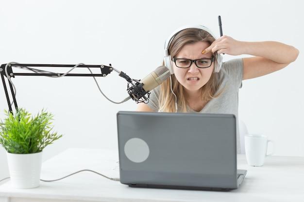 Conceito de apresentador de rádio, streamer e blogger - mulher trabalhando como apresentadora de rádio em uma estação de rádio sentada