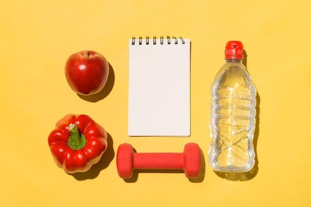 Conceito de aptidão. coleção de frutas frescas com halteres e garrafa de água em fundo amarelo.