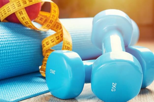 Conceito de aptidão com halteres azuis, tapete de fitness e uma fita métrica, close-up