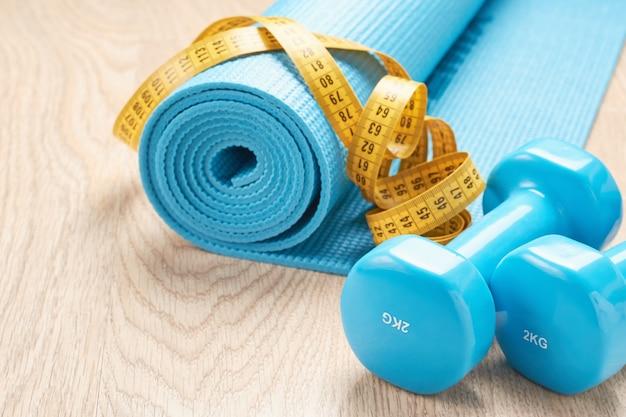 Conceito de aptidão com halteres azuis, tapete de fitness e uma fita métrica, cópia espaço