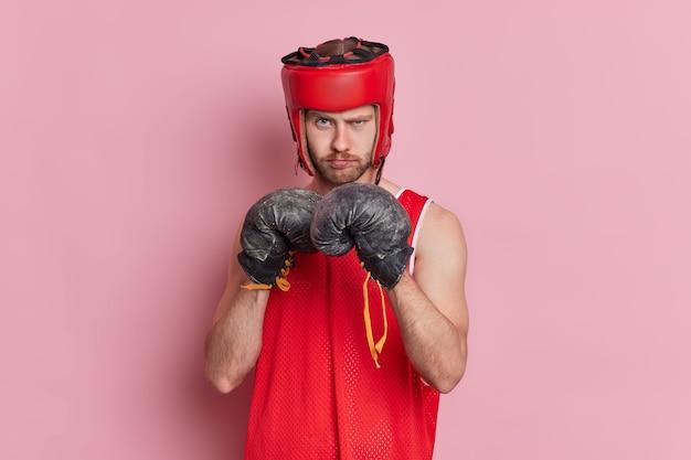 Conceito de aptidão do esporte de pessoas. homem europeu sério e confiante musculoso com a barba por fazer e usa luvas de boxe e capacete protetor