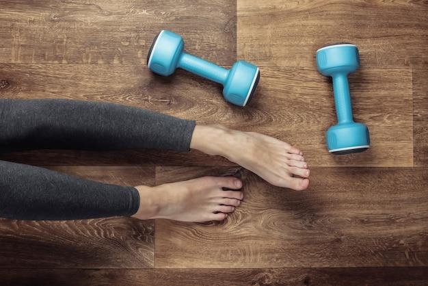 Conceito de aptidão. pernas femininas em leggings e pés descalços sentam-se no chão com halteres.
