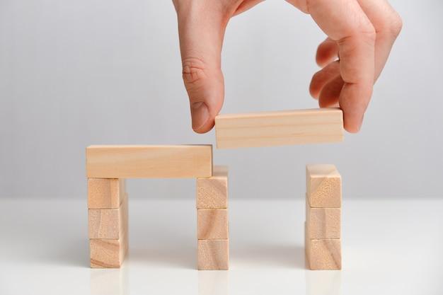 Conceito de aquisição de negócios. mão segura blocos de madeira em um espaço em branco.