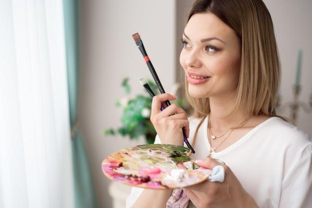 Conceito de arte, criatividade, hobby, trabalho e ocupação criativa. artista feminina posando em frente a uma janela e pintando com tinta acrílica ou óleo