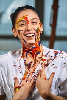 Conceito de arte de beleza, retrato de uma jovem garota pintada com cores diferentes de tinta. demonstrações coloridas, retrato colorido, reprodução de cores, todas as cores reunidas em uma. close-up, cópia espaço