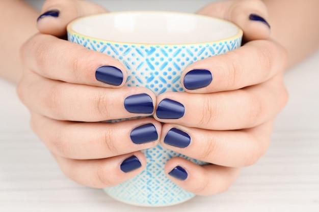 Conceito de arte do prego. lindas mãos femininas com manicure elegante, segurando a xícara, close-up