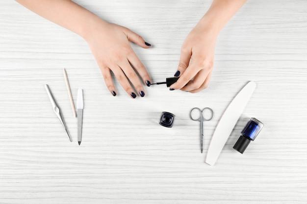 Conceito de arte do prego. mulher fazendo manicure na mesa branca