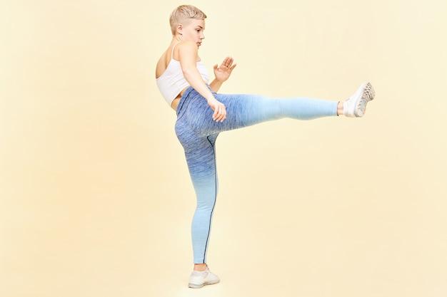 Conceito de artes marciais, karatê e kung fu. imagem de corpo inteiro da lutadora de mma loira durona de top, leggings e tênis treinando dentro de casa chutando o inimigo invisível com uma perna estendida