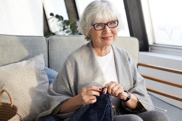 Conceito de artesanato, hobby, idade e aposentadoria. mulher idosa linda e elegante com rugas e cabelos curtos grisalhos aproveitando o tempo de lazer, sentada na sala de estar e tricotando um lenço estiloso para si mesma