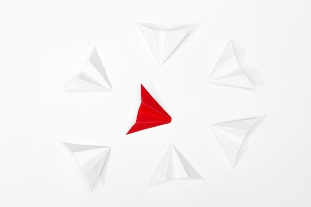 Conceito de assédio. avião de papel vermelho é cercado por brancos
