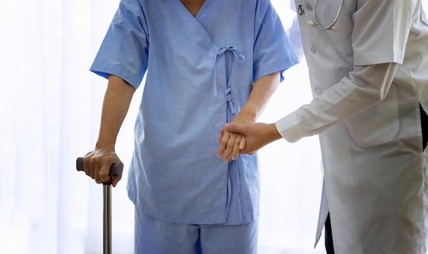 Conceito de atendimento ao paciente idoso; doutor asiático que apoia a mulher paciente idosa em usar o caminhante no hospital.
