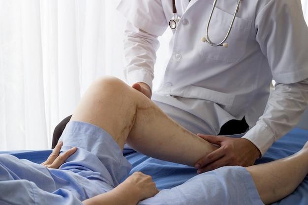 Conceito de atendimento ao paciente idoso; o doutor asiático está tomando a mulher paciente idosa no hospital.