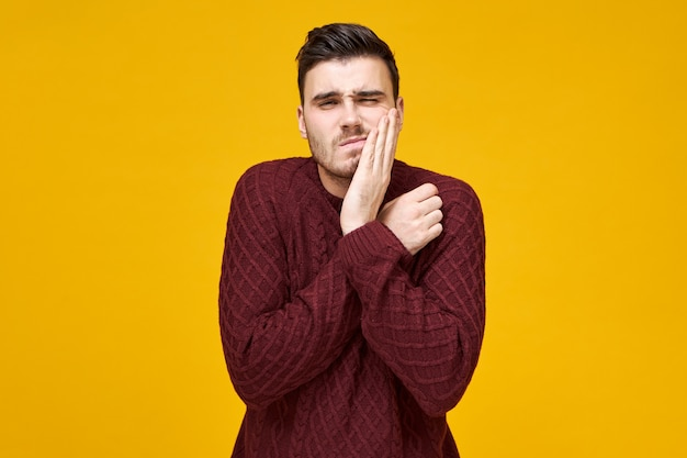 Conceito de atendimento odontológico, odontologia e estomatologia. retrato de um jovem chateado e estressado com dor de dente ou gengiva inflamada, pressionando a mão contra sua bochecha,
