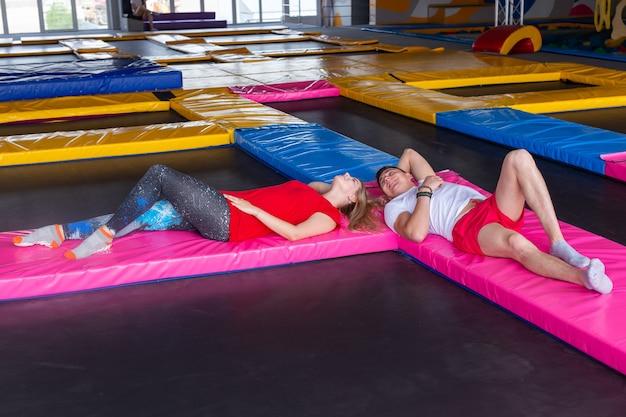 Conceito de atividade física, diversão, lazer e esporte - homem e mulher deitados juntos em um trampolim dentro de casa
