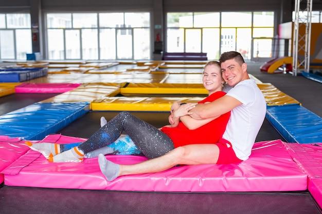 Conceito de atividade física, divertida, de lazer e esporte - casal feliz e alegre sentado em um trampolim dentro de casa