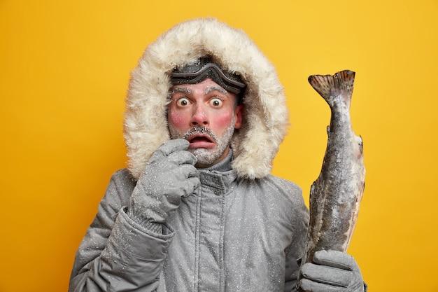 Conceito de atividades e hobbies de inverno ao ar livre. homem estupefato com o rosto vermelho e congelado encara os olhos esbugalhados segurando peixes grandes vestidos com roupas quentes tem uma pesca bem-sucedida.
