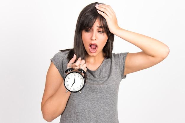 Conceito de atraso, minuto à meia-noite, preocupação e ansiedade. mulher segurando o relógio e a cabeça parecendo preocupada.