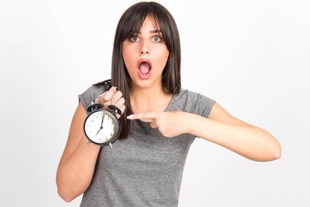 Conceito de atraso, minuto à meia-noite, preocupação e ansiedade. mulher segurando o relógio parecendo preocupada.