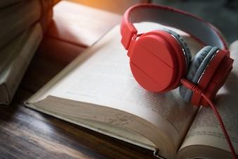 Conceito de audiobook. Livros na mesa com fones de ouvido colocados sobre eles.
