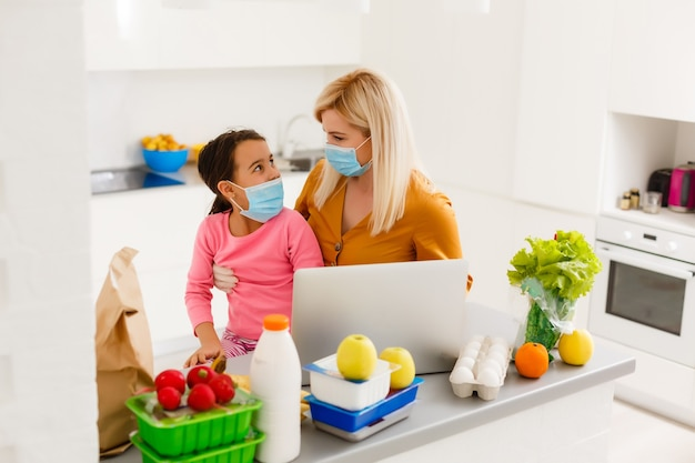 Conceito de auto-isolamento. mãe e filha desempacotando saco de papel com comida na cozinha, pronta para quarentena durante surto epidêmico