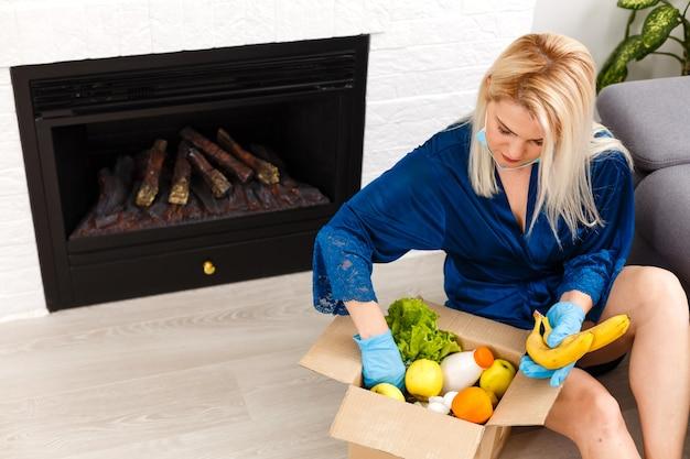 Conceito de auto-isolamento. mulher desempacotando um saco de papel com comida na cozinha, pronto para quarentena durante o surto epidêmico