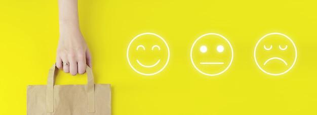 Conceito de avaliação do serviço ao cliente. saco de compra de papel pardo reciclado na mão com ícone de emoção de rosto de holograma em fundo amarelo, plano leigo. conceito de venda de verão. conceito de serviço de entrega.