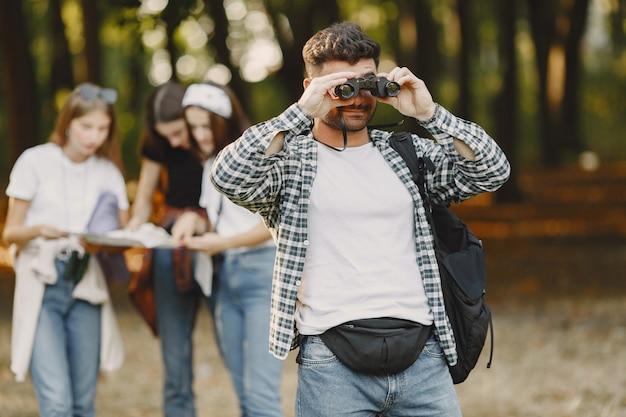 Conceito de aventura, caminhada e pessoas. grupo de amigos sorridentes em uma floresta. homem com binóculos.