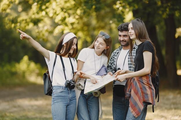 Conceito de aventura, viagem, turismo, caminhada e pessoas. grupo de amigos sorridentes em uma floresta. homem com binocular.