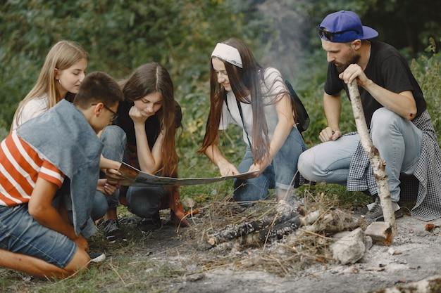 Conceito de aventura, viagem, turismo, caminhada e pessoas. grupo de amigos sorridentes em uma floresta. pessoas sentadas perto da fogueira.