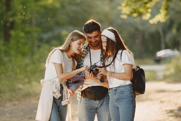 Conceito de aventura, viagem, turismo, caminhada e pessoas. grupo de amigos sorridentes em uma floresta.