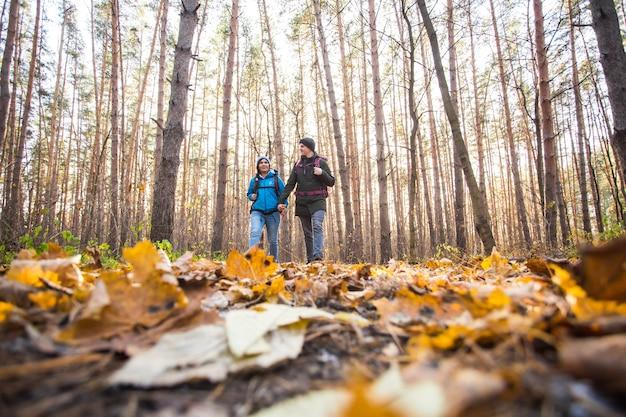 Conceito de aventura, viagem, turismo, caminhada e pessoas - jovem casal com mochilas na floresta.