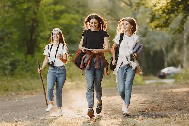 Conceito de aventura, viagem, turismo, caminhada e pessoas. três garotas em uma floresta.