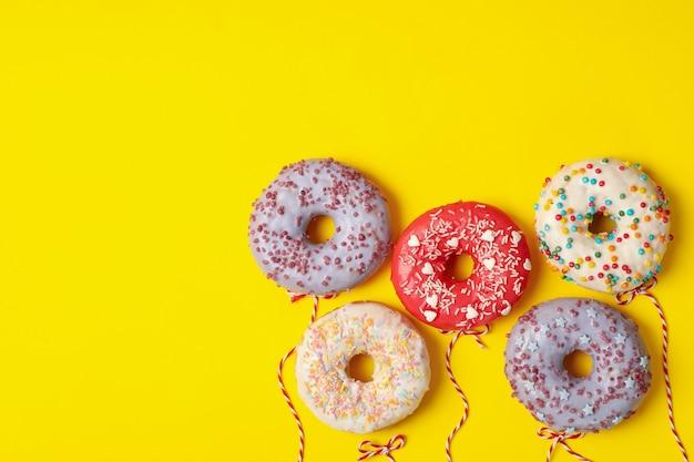 Conceito de balões feitos de donuts em fundo amarelo
