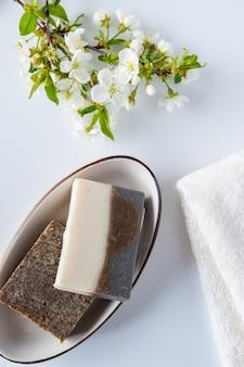 Conceito de banho e cosméticos naturais. barras de sabão artesanal e toalhas na mesa branca. spa e cuidados com o corpo