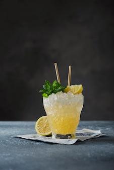 Conceito de bar: coquetel amarelo com limão, hortelã e gelo picado na parede preta, imagem de foco seletivo