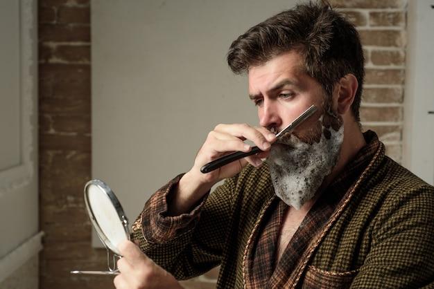 Conceito de barbearia. cabeleireiro faz penteado um homem com barba. cliente barbudo visitando a barbearia. cuidado com a barba. homem sênior visitando cabeleireiro em barbearia