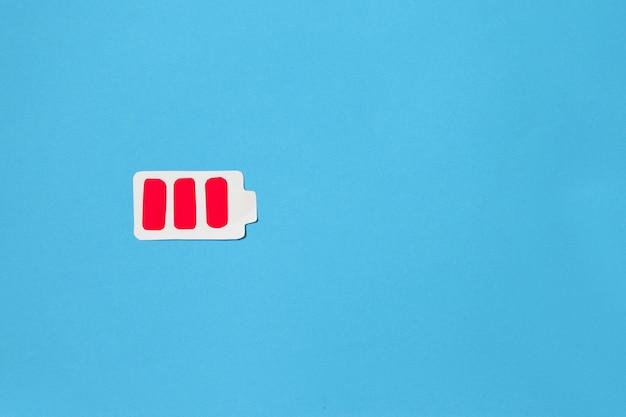 Conceito de bateria fraca. figura de papel da bateria em um fundo azul