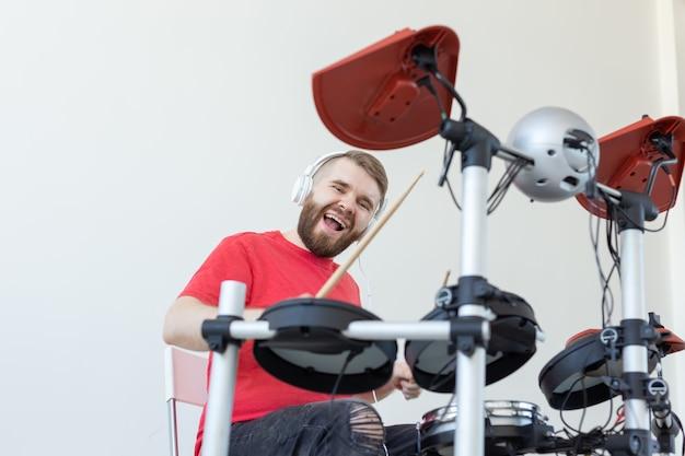 Conceito de baterista, hobbies e música - jovem baterista de camisa vermelha tocando bateria eletrônica.