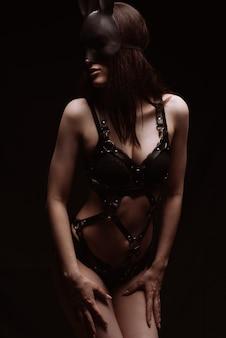 Conceito de bdsm. garota sexy em lingerie de couro preta e uma máscara de coelhinho