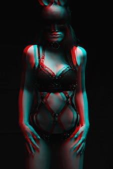 Conceito de bdsm. garota sexy em lingerie de couro preta e uma máscara de um coelho.