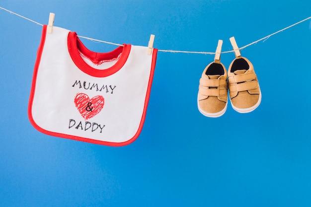 Conceito de bebê com babador e sapatos pendurados no varal