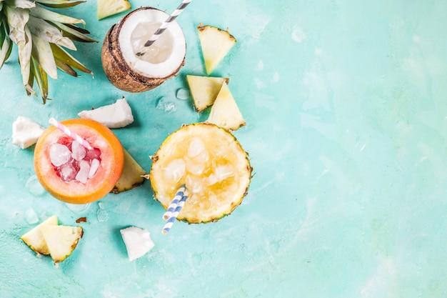 Conceito de bebida nas férias de verão, defina vários coquetéis tropicais ou sucos em abacaxi, toranja e coco com gelo, concreto azul claro