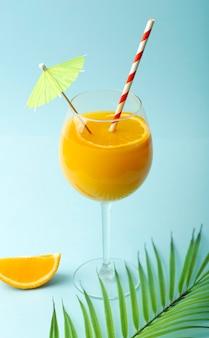 Conceito de bebidas de verão. suco de laranja em um copo de vidro em um fundo azul colorido. fundo mínimo de verão tropical