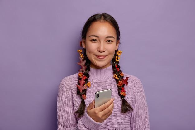 Conceito de bela temporada. mulher asiática atraente tem beleza natural, cabelo escuro penteado em duas tranças com folhas caídas de outono, gosta de aconchego outonal, usa smartphone moderno nas horas de lazer