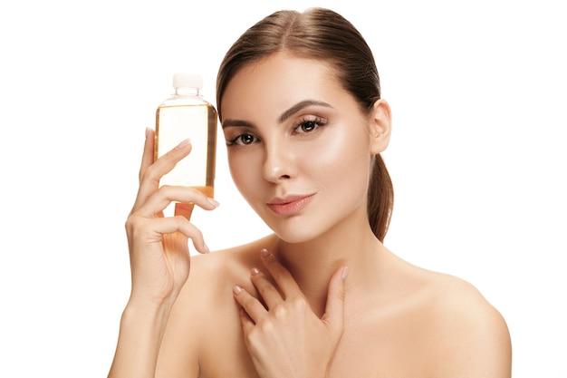 Conceito de beleza. a mulher bonita caucasiana com pele perfeita, segurando o frasco de óleo no estúdio. o conceito de beleza, cuidados, pele, tratamento, saúde, spa, cosméticos e publicidade