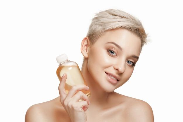 Conceito de beleza: a mulher bonita com pele perfeita segurando um frasco de óleo