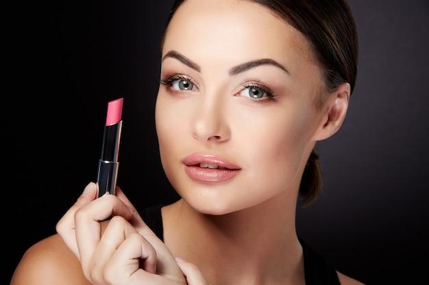 Conceito de beleza, cabeça e ombros de jovem olhando para a câmera e segurando batom rosa. closeup retrato de modelo com lábios rosados, estúdio com fundo preto
